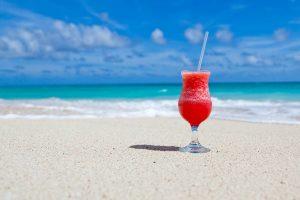 Bicchiere cocktail rosso alla fragola solo su spiaggia caraibica.